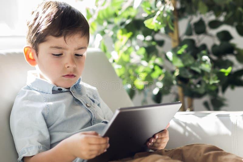 Мальчик с цифровым планшетом сидя на софе, на домашней внутренней предпосылке стоковое фото rf