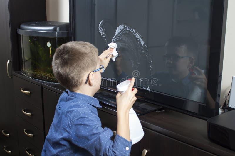 Мальчик убирая комната Он прикладывает тензид для мебели с аппликатором В другой руке, он держит белую обтирая ткань стоковые изображения rf