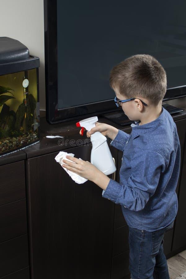 Мальчик убирая комната Он прикладывает тензид для мебели с аппликатором В другой руке, он держит белую обтирая ткань стоковые изображения