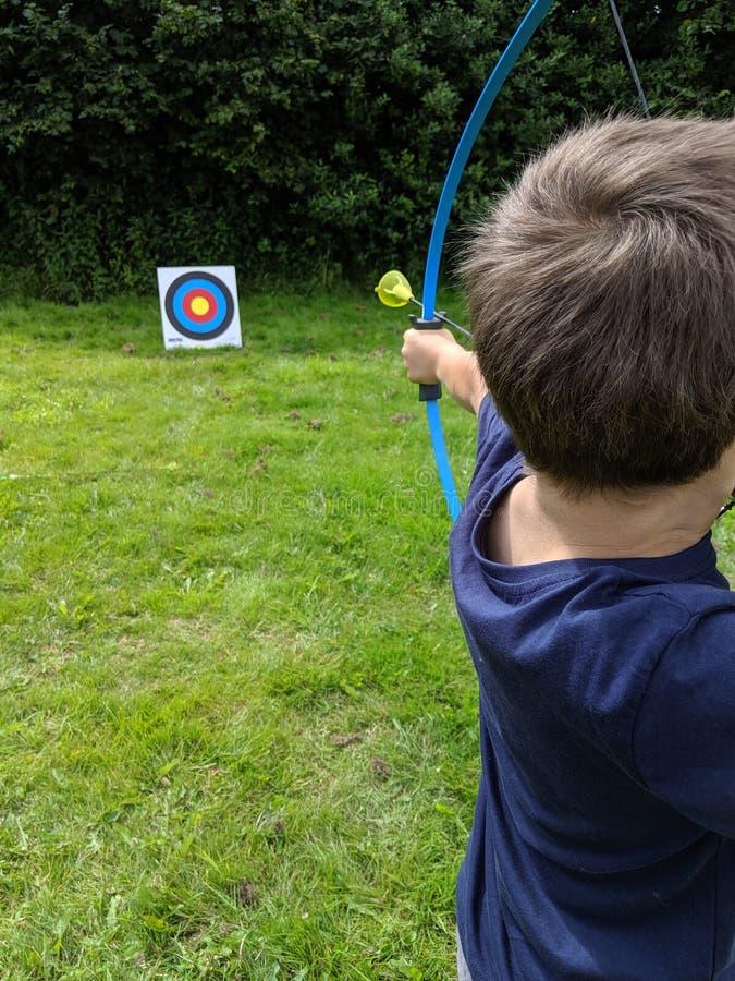 Мальчик увольняет дротик стрелки на цели с его смычком стоковая фотография rf