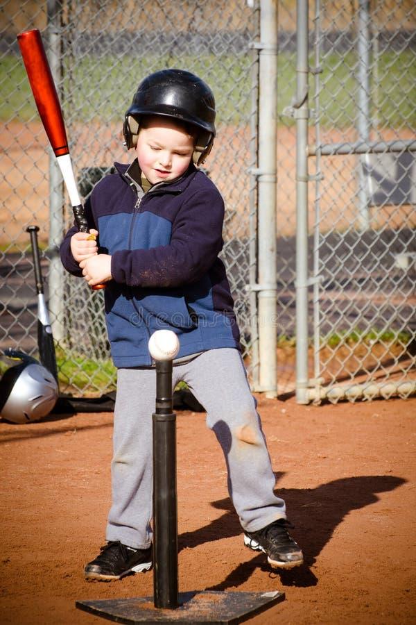 Мальчик ударяя бейсбол стоковое изображение