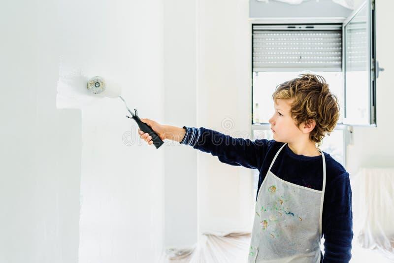 Мальчик украшает свой новый дом, красляя стены своей комнаты белым, грязно замазая стоковые фото