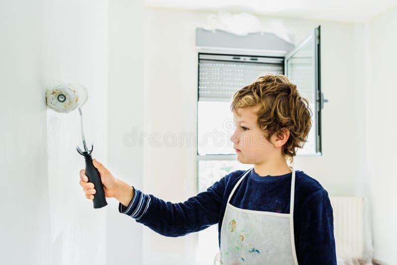 Мальчик украшает свой новый дом, красляя стены своей комнаты белым, грязно замазая стоковые фотографии rf