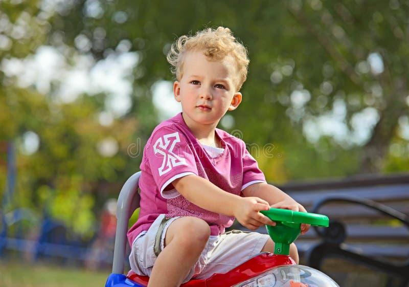 мальчик управляя его маленьким кораблем игрушки стоковая фотография rf