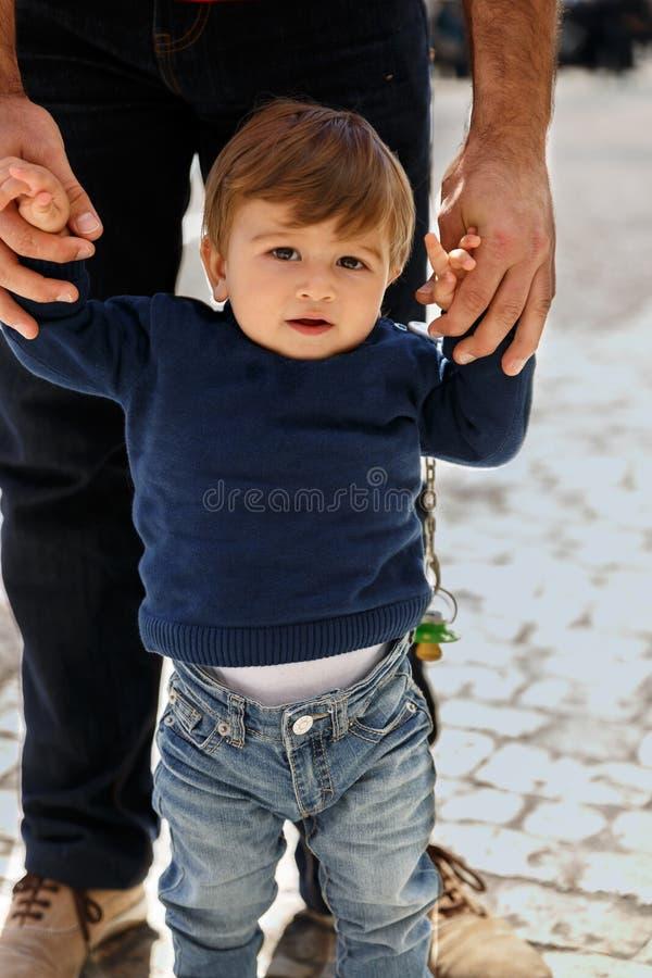 Мальчик уча идти от руки взрослого стоковое изображение