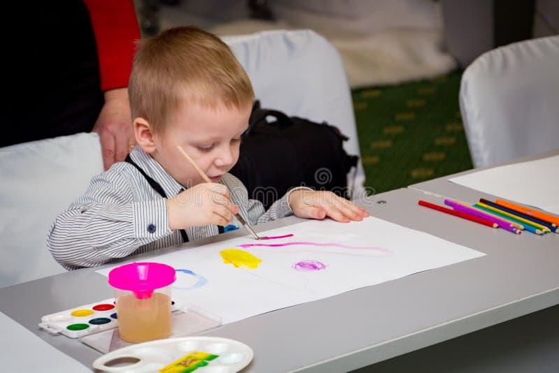 Мальчик учит покрасить с щеткой стоковые изображения