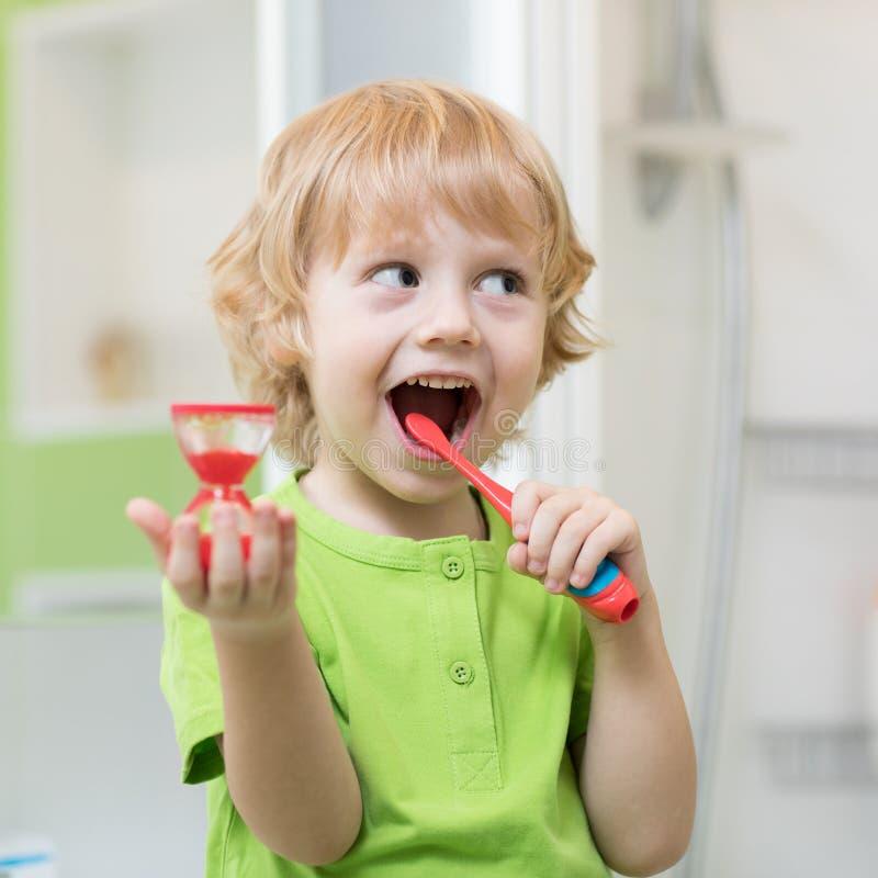 Мальчик чистит его зубы щеткой контролируя продолжать с часами стоковое изображение