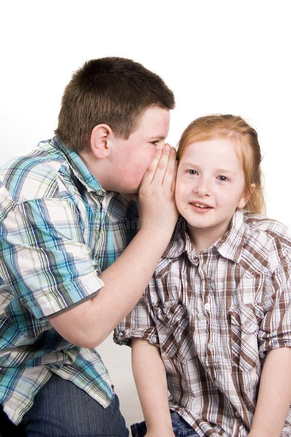 Мальчик шепчет в ухе девушок стоковое фото rf