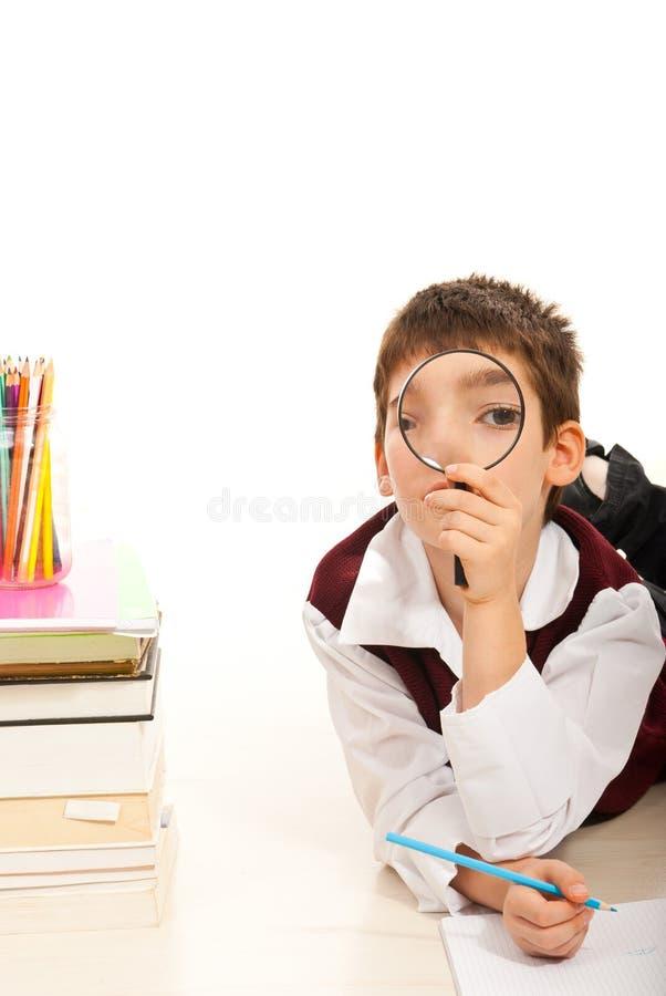 Мальчик школы смотря повсеместно в loupe стоковое фото rf