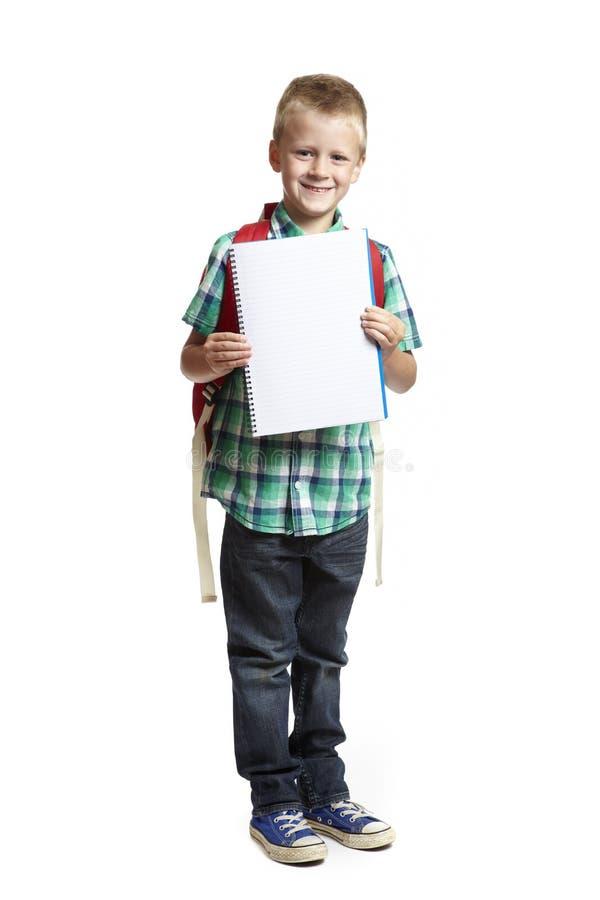 Мальчик школы с блокнотом на белой предпосылке стоковые изображения rf
