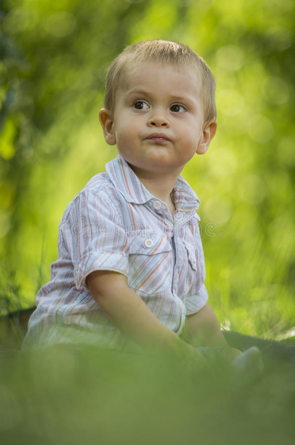 Мальчик ый в зеленом парке стоковые фотографии rf