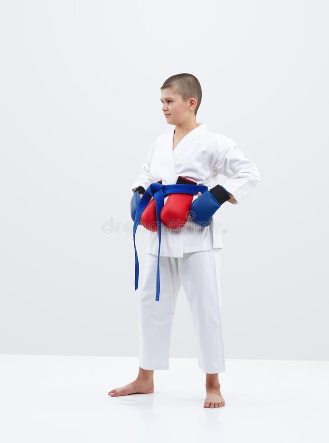 Мальчик Karateka с голубыми верхними слоями на руках и красными верхними слоями за поясом стоковые изображения