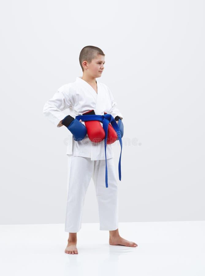 Мальчик Karateka с голубым поясом и верхними слоями на светлой предпосылке стоковое фото rf