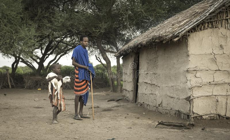 Мальчик Maasai нося козу младенца стоковое фото rf