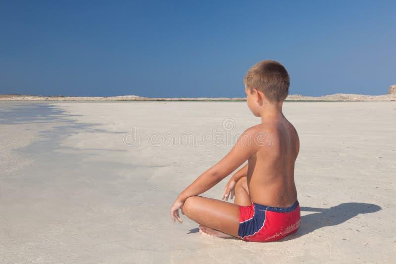 Мальчик meditating на пляже стоковое изображение rf