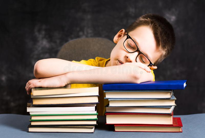 Мальчик sleepeing na górze книг стоковое фото