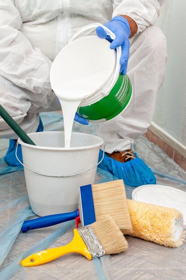 Маляр на работе подготавливает белую краску стоковые фотографии rf