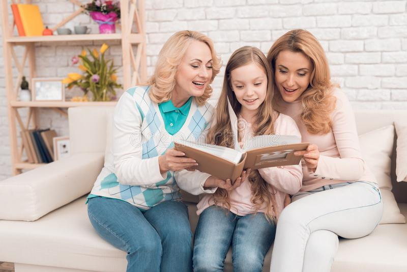 Мама, бабушка и девушка рассматривают альбом семьи стоковые фото