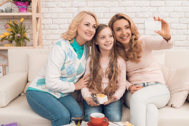Мама, бабушка и маленькая девочка делают selfie сидя на кресле стоковые фотографии rf