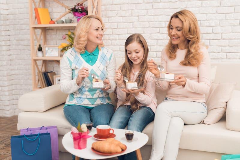 Мама, бабушка и маленькая девочка едят торт на кресле стоковая фотография