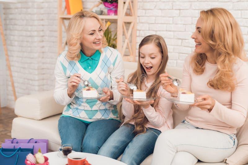 Мама, бабушка и маленькая девочка едят торт на кресле стоковые фотографии rf