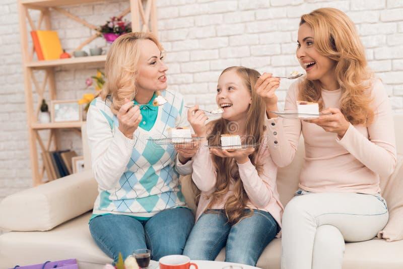 Мама, бабушка и маленькая девочка едят торт на кресле стоковая фотография rf