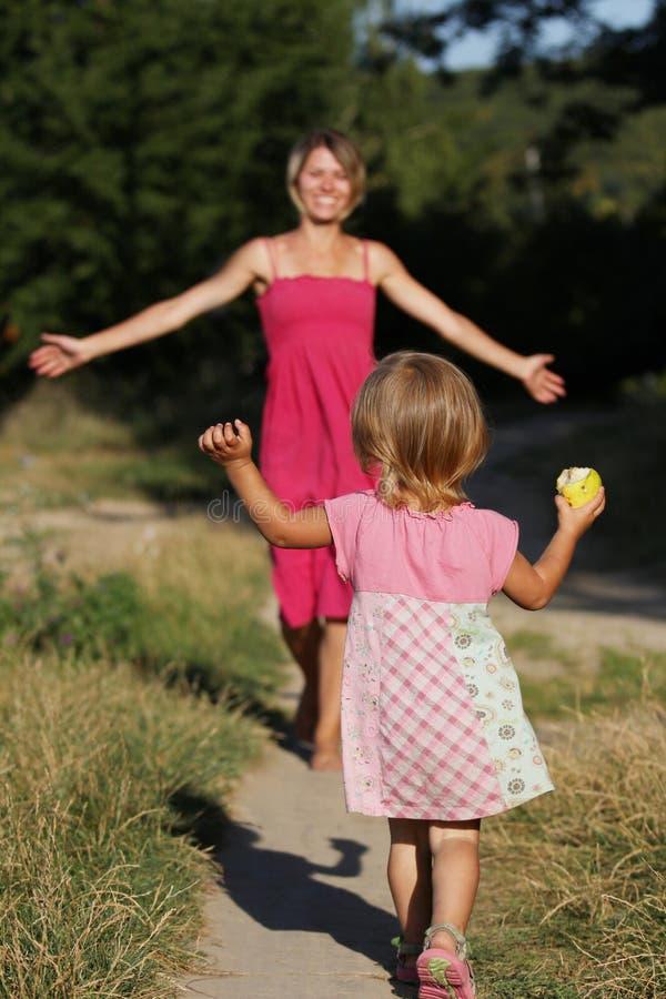 Мама бежит вне для того чтобы встретить ее маленькую дочь стоковые изображения