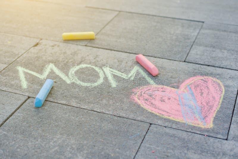 Мама влюбленности Чертеж ` s детей покрасил crayons на асфальте стоковые фото