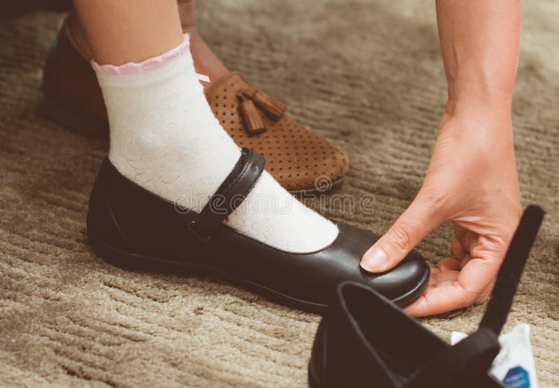 Мама выбирает ботинки для ее daughte стоковая фотография rf