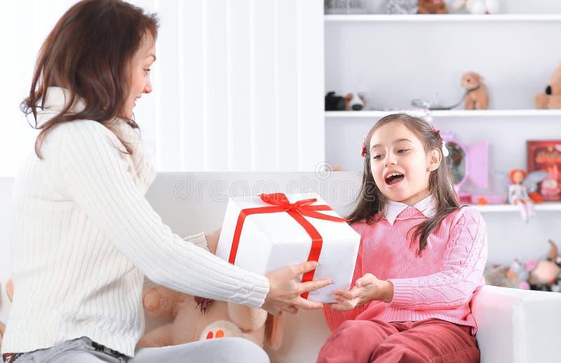 Мама дает ее дочери коробку с подарком на день рождения стоковая фотография rf