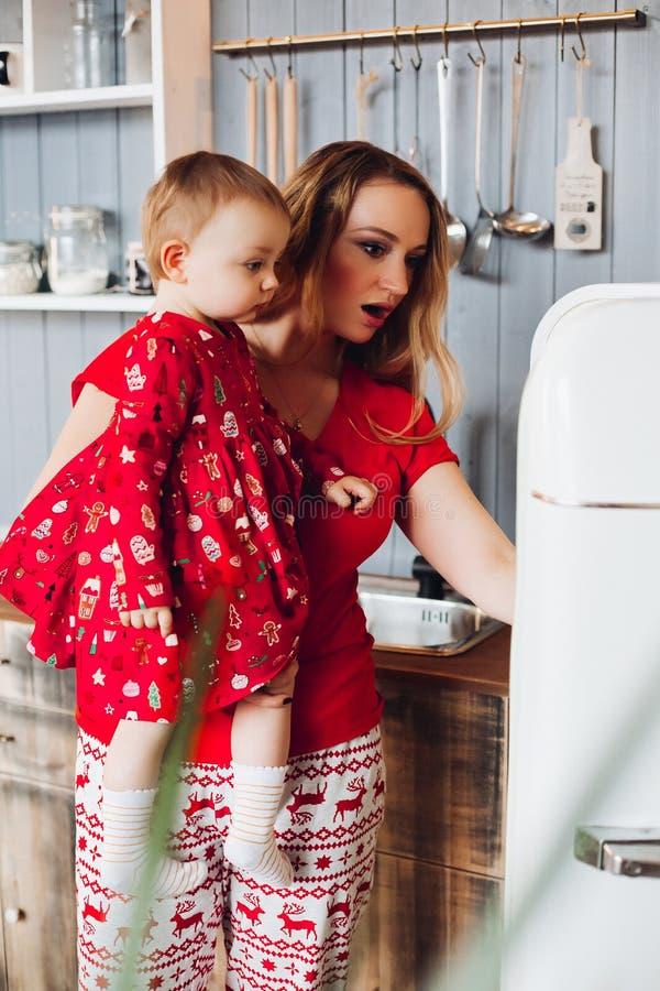Мама держа вручную маленькую дочь, показывая и смотря внутренний холодильник стоковое изображение