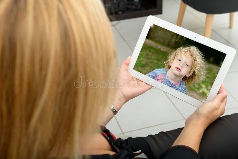 Мама звоня дистантный на интернете стоковые изображения