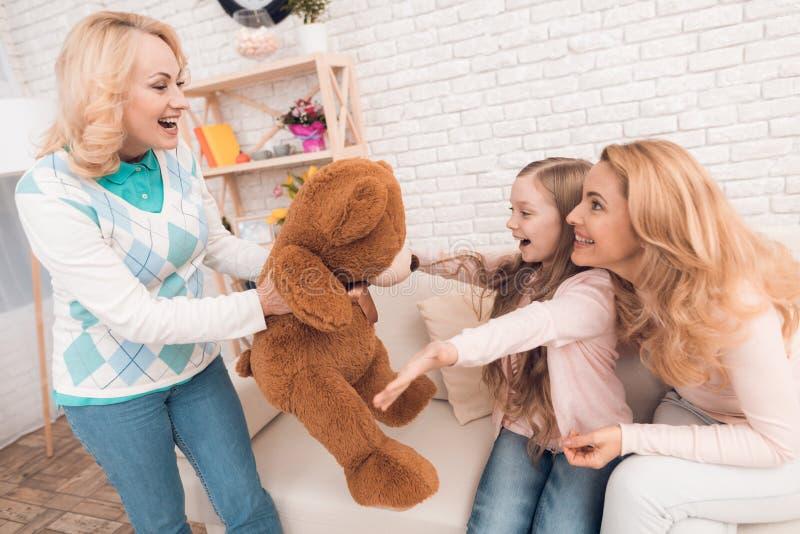 Мама и бабушка дают маленькой девочке большого медведя игрушки стоковые изображения rf
