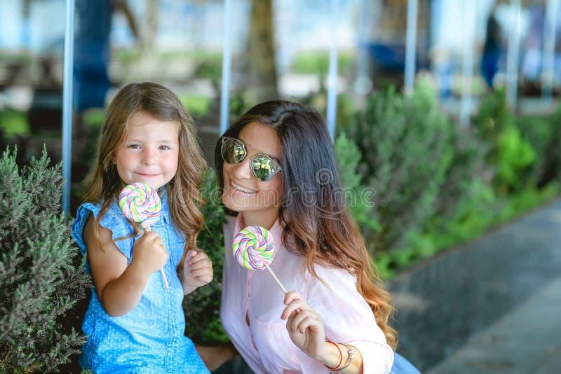 Мама и девушка есть конфету в парке стоковая фотография rf