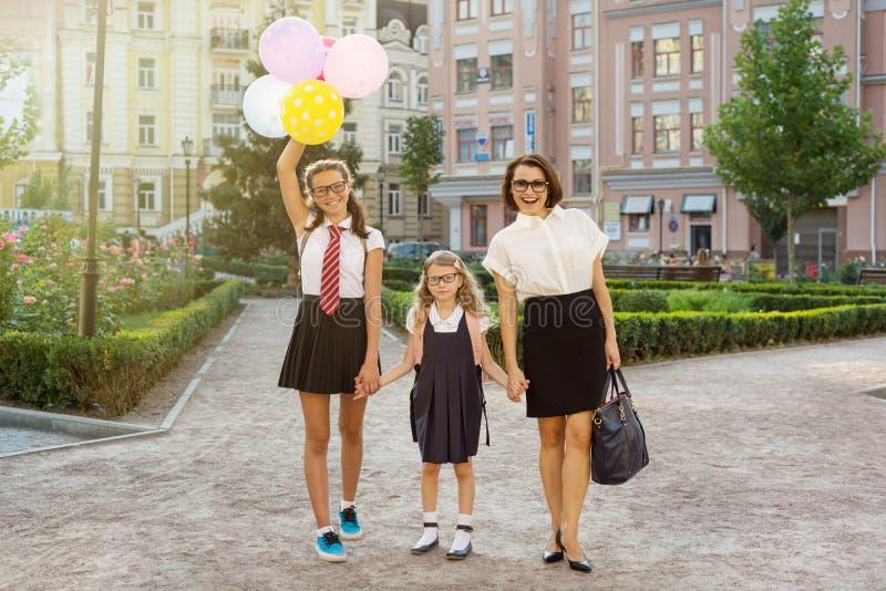 Мама и дети держа руки, идут к школе стоковые изображения