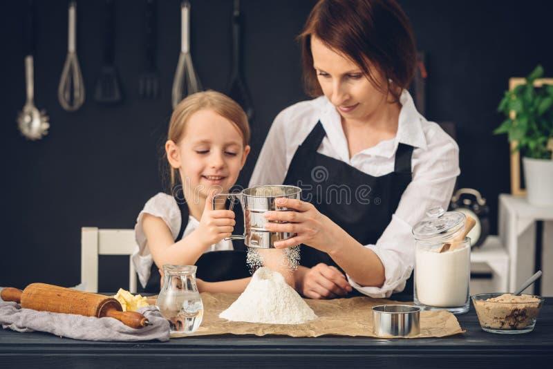 Мама и дочь подготавливая вареники в кухне стоковое фото