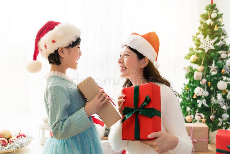 Мама и ее девушка дочери обменивая подарки стоковые изображения