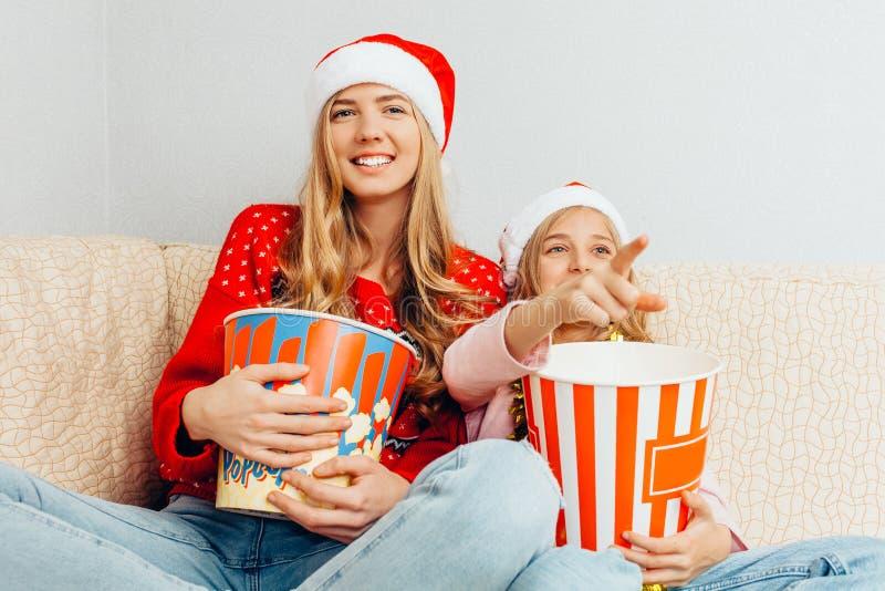 Мама и ее маленькая дочь, одетые в шляпах Санта Клауса, дозор стоковые изображения rf