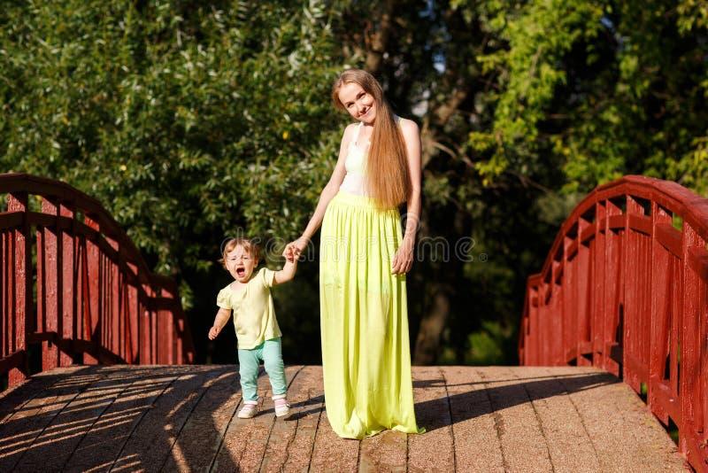 Мама и маленькая дочь вручную идут на деревянный мост стоковое изображение
