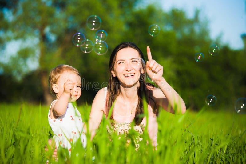 Мама и маленькая дочь жизнерадостно улавливая пузыри мыла стоковые фото