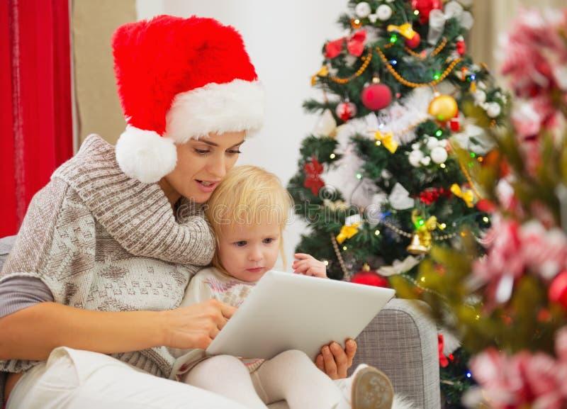 Мама и младенец используя ПК таблетки около рождественской елки стоковое изображение rf
