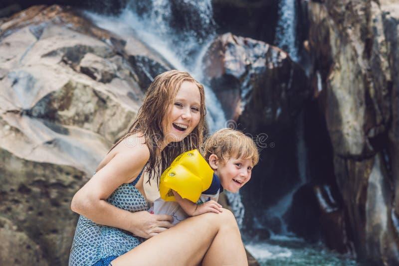 Мама и молодой сын на предпосылке водопада Путешествовать с ki стоковые изображения rf