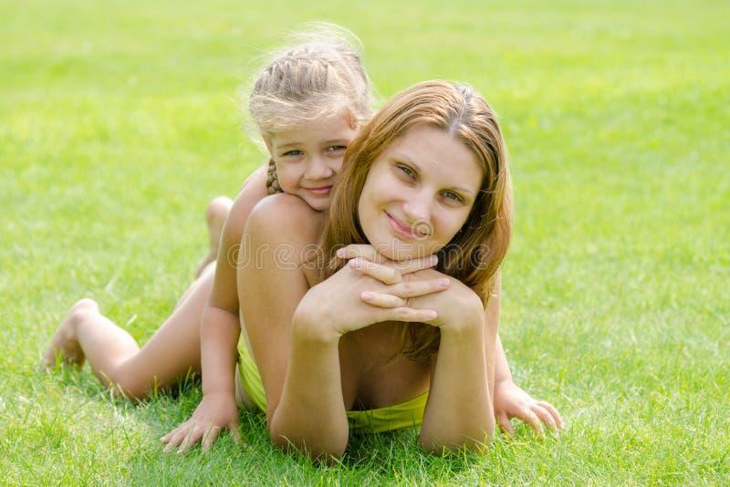 Мама и дочь лежат на зеленой лужайке в бикини и смотрят в рамке стоковая фотография