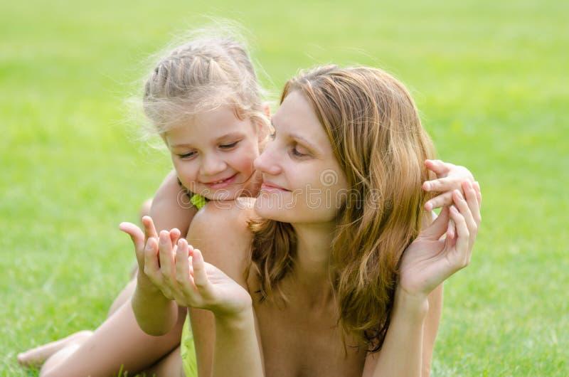 Мама и дочь имея пикник лета объятия потехи на зеленой лужайке стоковые изображения rf