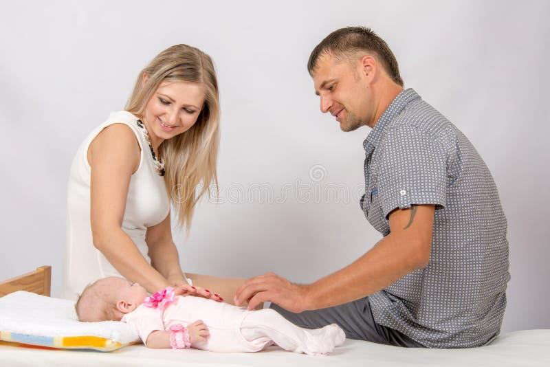 Мама и папа сидят на кровати на которой положение их младенец стоковая фотография rf