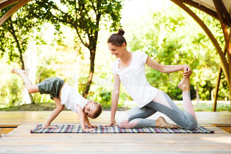 Мама и сын практикуют йогу в парке стоковые фотографии rf