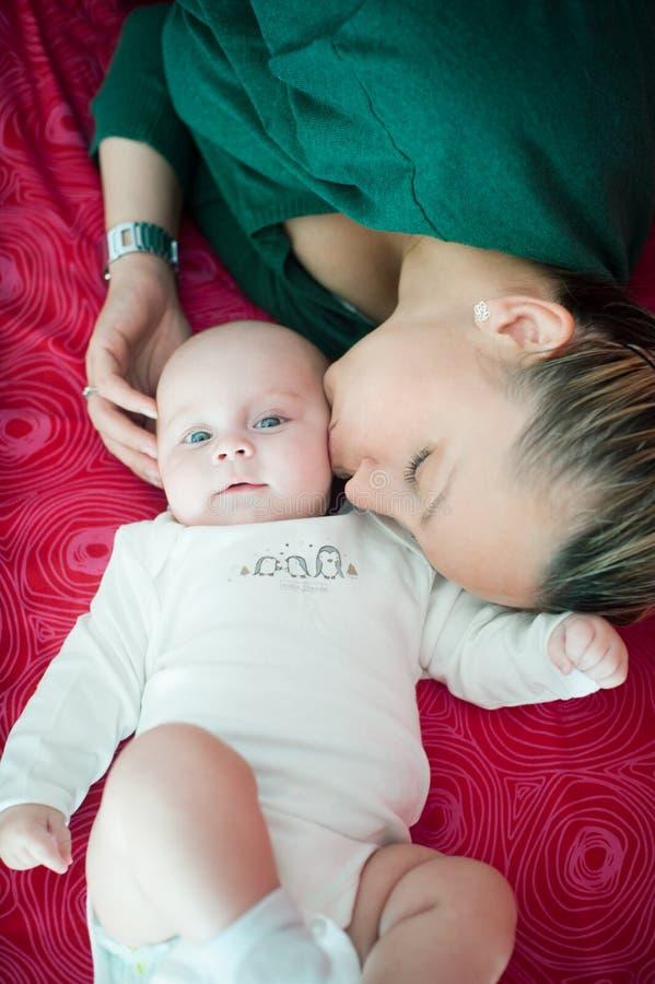 Мама нежно целует ее дочь стоковое изображение