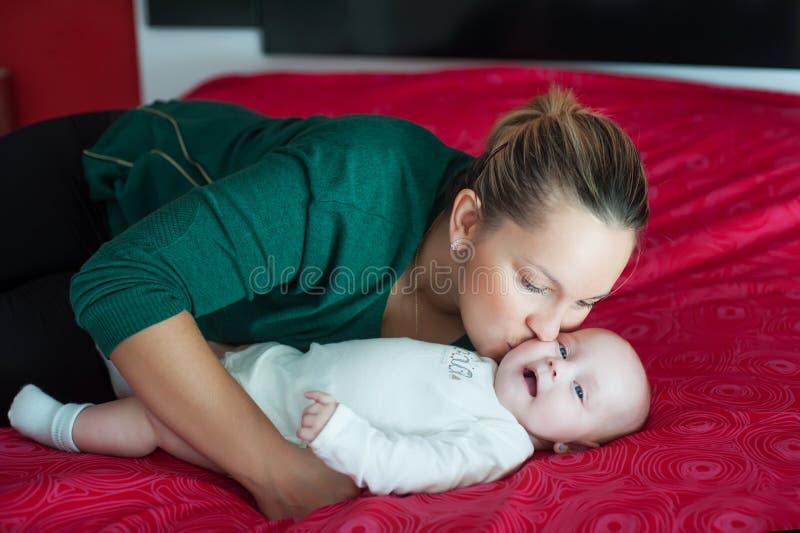 Мама нежно целует ее дочь стоковое фото rf