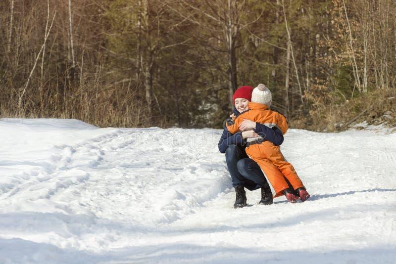 Мама обнимает небольшого сына на предпосылке дня зимы соснового леса снежного в coniferous лесе стоковое фото rf