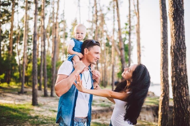 Мама, папа и дочь семьи сидят на папе на плечах, и родители целуют на природе в лесе летом на стоковая фотография